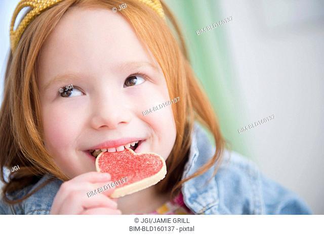 Caucasian girl eating heart-shape cookie