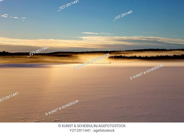Vapors rising from a frozen lake are illuminated by the setting sun. Agnsjön, Bredbyn, Västernorrland, Sweden