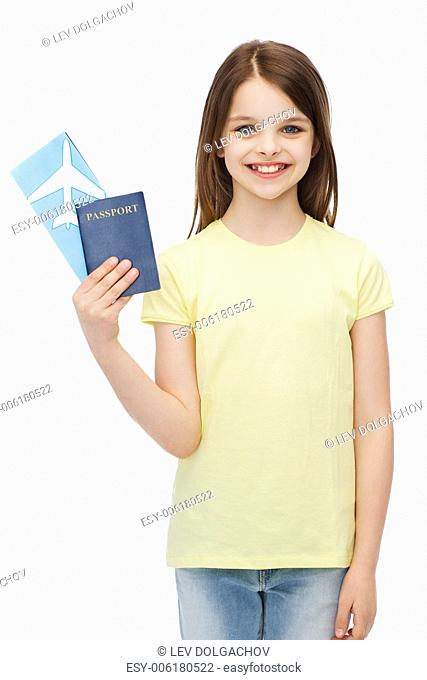 travel, holiday, vacation, childhood and transportation concept - smiling little girl with airplane ticket and passport