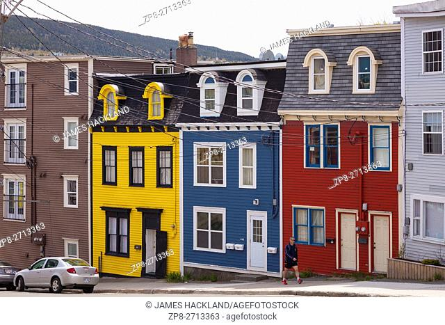 A person passing by colourful row houses (Jellybean Row) in downtown St. John's, Avalon Peninsula, Newfoundland, Canada