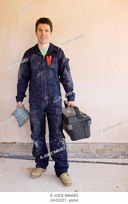Smiling man in coveralls holding spool of electrical cable and toolbox