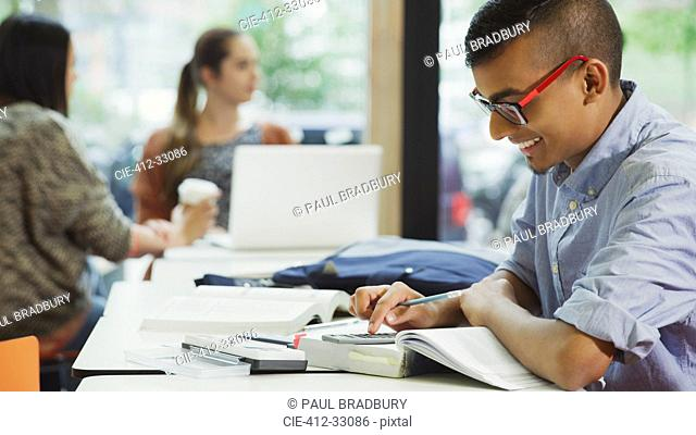 Male college student doing math homework with textbook and calculator