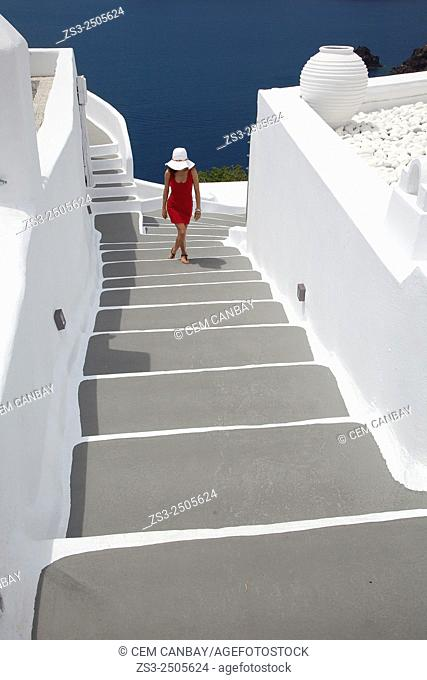 Woman walking up the steps in Oia town, Santorini, Cyclades Islands, Greek Islands, Greece, Europe