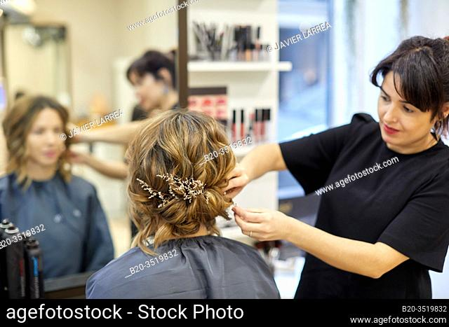 Hairdresser placing ornaments on a woman's hair, hairdressing salon and beauty clinic