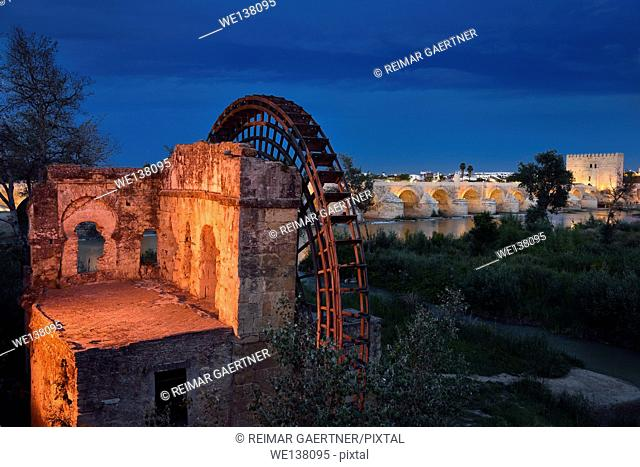 Lights on Albolafia Waterwheel at dusk on the Guadalquivir river with Roman Bridge and Calahorra Tower Cordoba