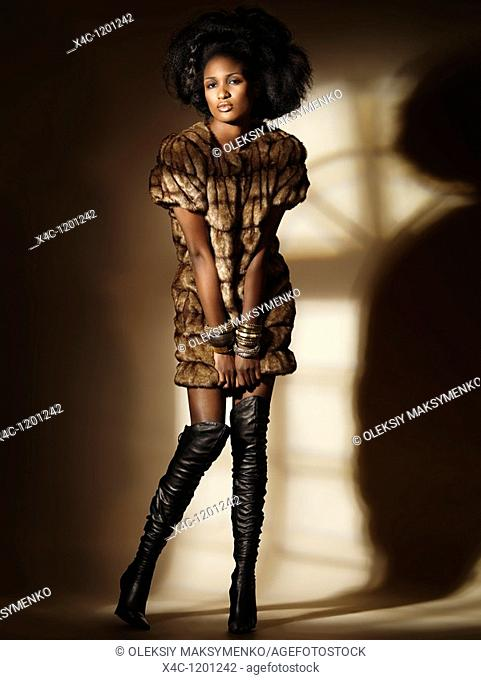 High fashion photo of a young woman wearing a fur coat standing in light coming from a window