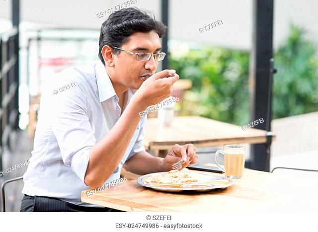 Asian Indian business man eating food at cafeteria