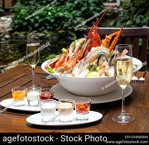 Bowl of gourmet fresh seafood on ice with savory sauce serve with white wine glass on vintage wooden table. Restaurant gastronomy food and drink consumerism...