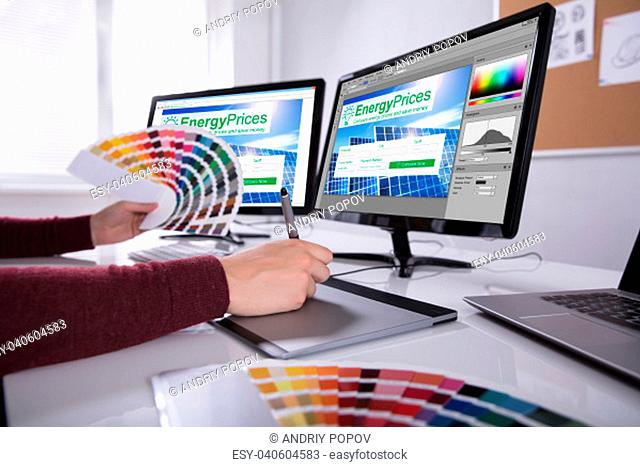 Side View Of A Young Male Designer Holding Colorful Swatch Working On Computer In Office