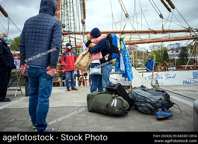 """26 April 2020, Schleswig-Holstein, Kiel: A mother hugs her son after the arrival of the sailing ship """"""""Thor Heyerdahl"""""""" in the port of Kiel"""