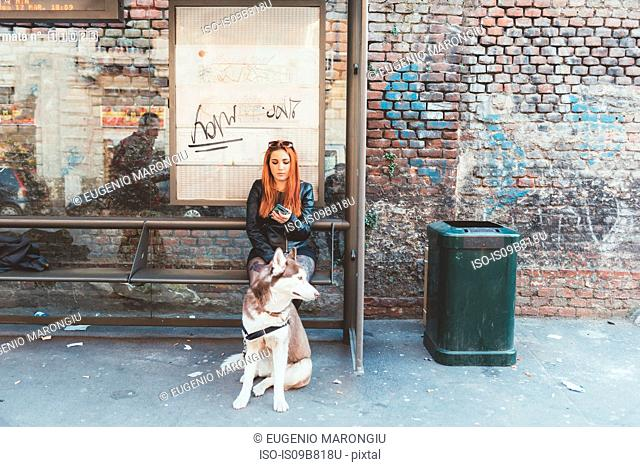 Red haired woman with dog waiting at bus stop