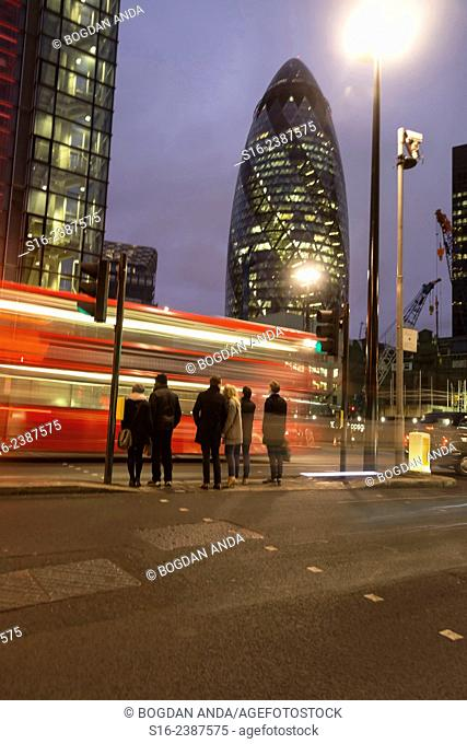 London, UK, The City - Red Double-decker bus zipping in front of pedestrians close to the Gherkin Building at night