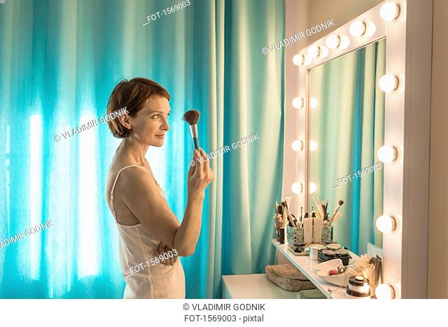 Woman holding make-up brush standing in front of mirror at dressing table