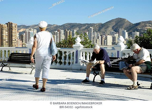 Two men read newspaper in a bench, balcony of the Mediterranean, Benidorm, Costa Blanca, Spain