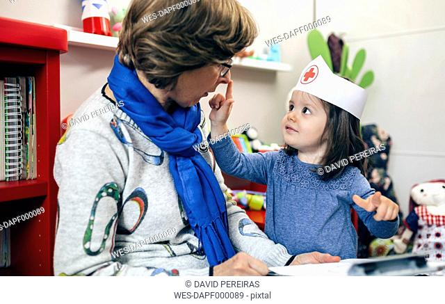 Little girl with nurse cap playing with her grandmother