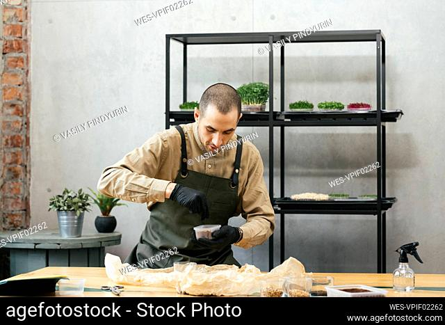 Portrait of man holding box with microgreens