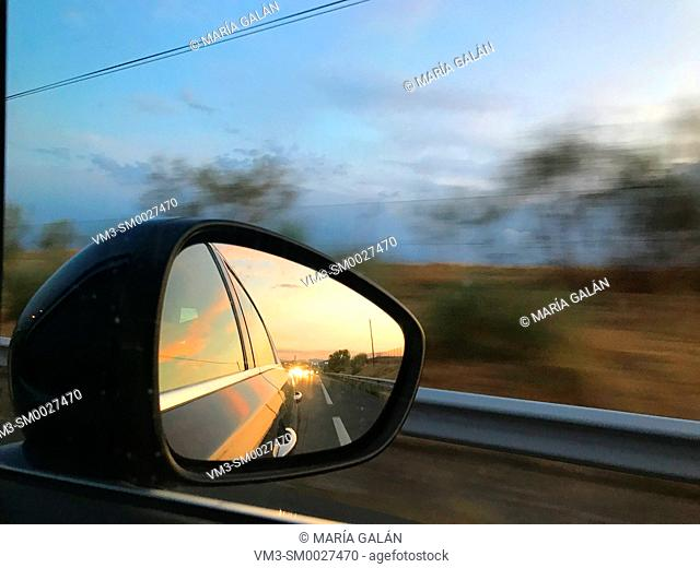 Road reflected on rear view mirror at dusk