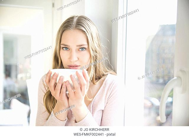 Portrait of blond woman with bowl of coffee