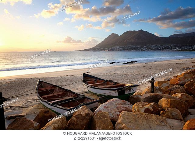 Landscape photo of two small fishing boats on a beach with Simonstown in the background. Cape Peninsula, Cape Town, South Africa