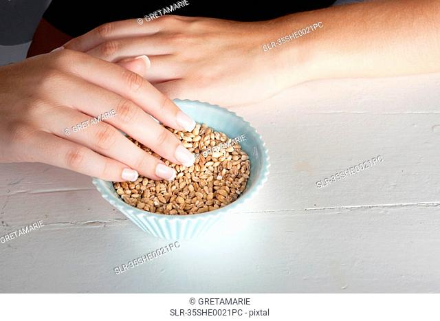 Woman touching bowl of grains