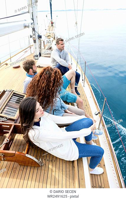 Group of friends relaxing on boat deck of yacht