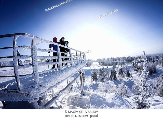 Caucasian snowboarders standing on snowy platform