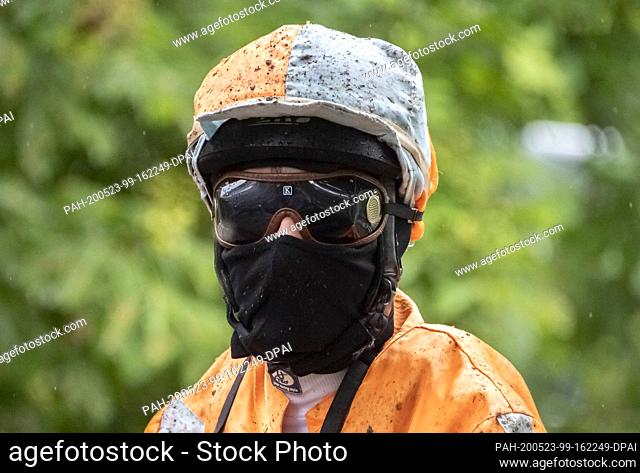 23 May 2020, Baden-Wuerttemberg, Iffezheim: A jockey wearing a protective mask leaves the track at the spring meeting at the Iffezheim racecourse after a race