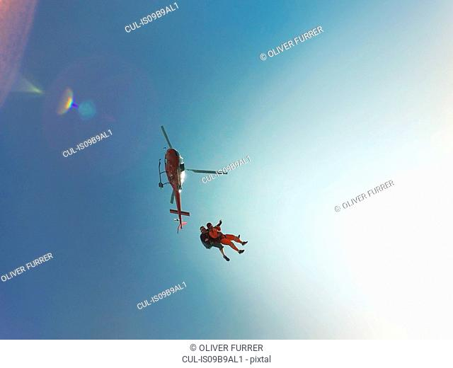 Low angle view of tandem skydiving jump from a helicopter against sunlit blue sky