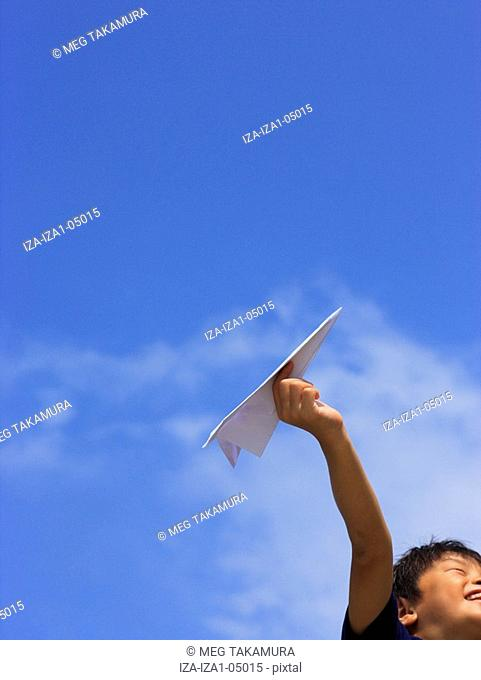 Low angle view of a boy holding a paper airplane and smiling