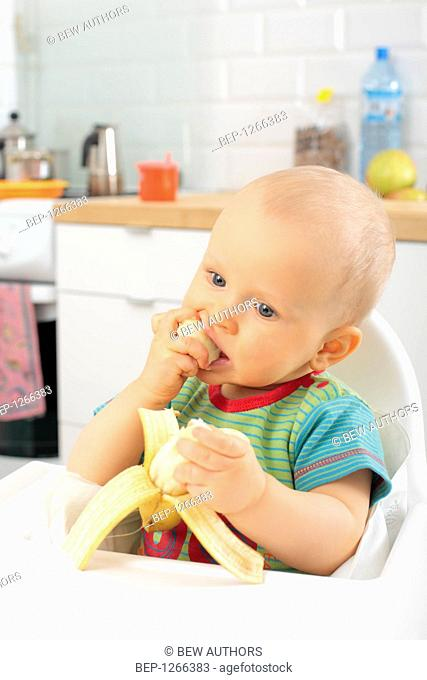 Little boy eating banana
