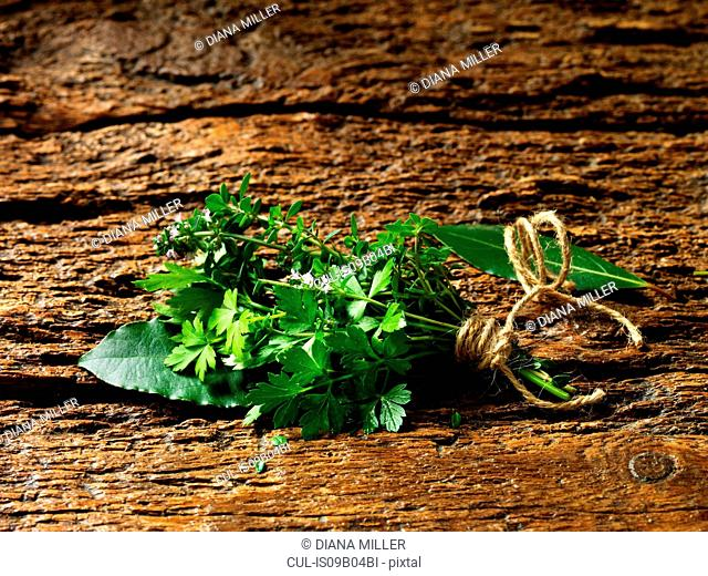 Parsley, thyme, bay leaves tied together with string on rustic wooden surface