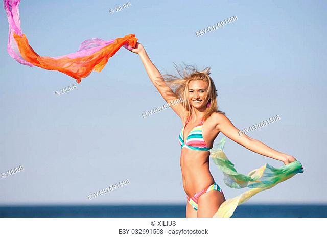 Beautiful blond woman with colorful scarf at the sea