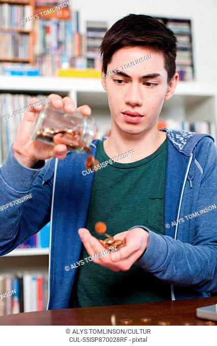 Young man emptying jar of coins