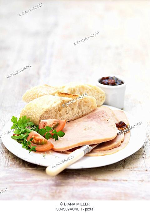 Sliced Danish ham and pickle, garnished with salad leaves and tomato with rustic sliced bread
