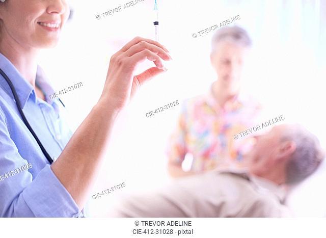 Doctor preparing syringe near senior man