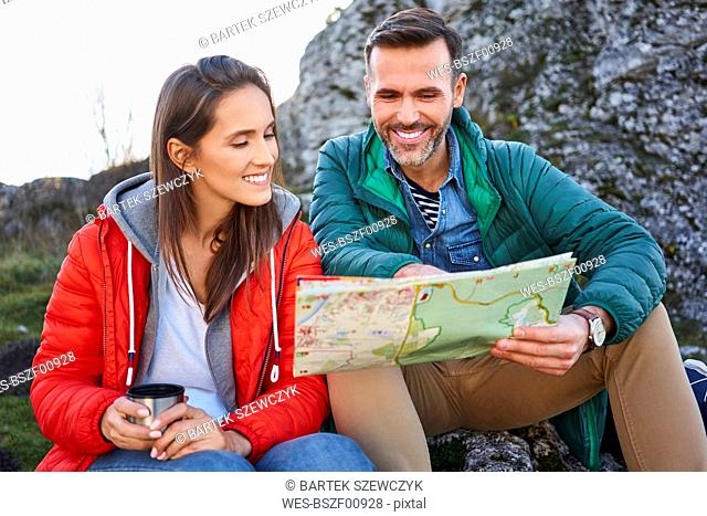 Happy couple on a hiking trip in the mountains taking a break looking at map