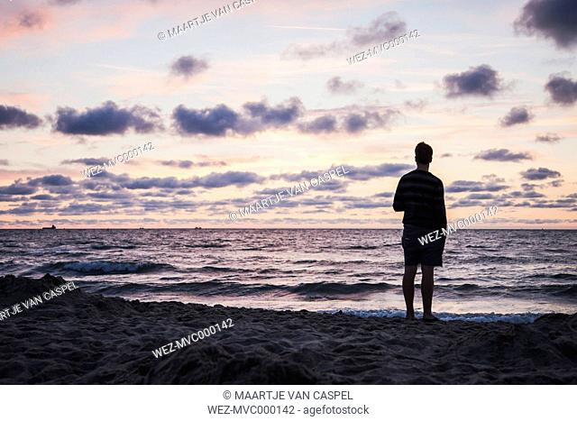 Silhouette of teenage boy standing on beach looking at the sea in front of evening sky