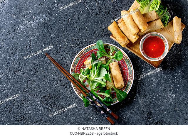 Fried spring rolls with red pepper sauces, served in traditional china plate with fresh green salad and wooden chopsticks over black texture background
