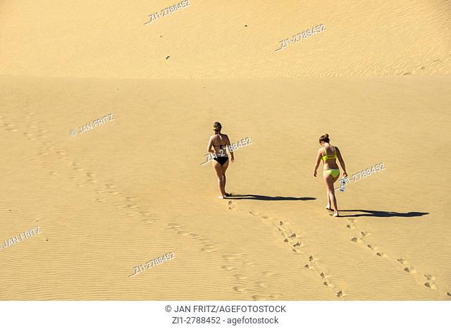 Two girls in bikini walking in sand dunes at Maspalomas, Grand Canaria, Spain