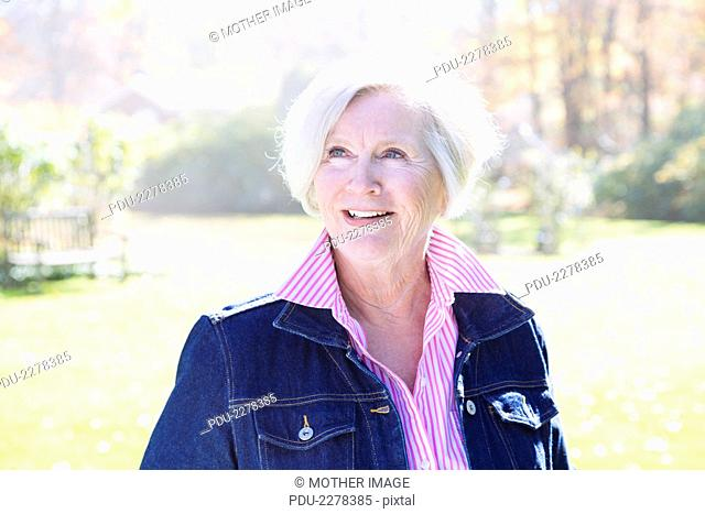 Fashionable Senior woman smiles off camera outside