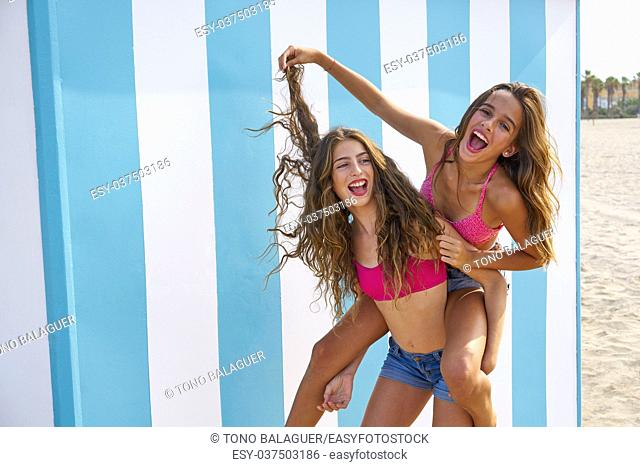 Best friends girls piggyback in summer beach with blue stripes background