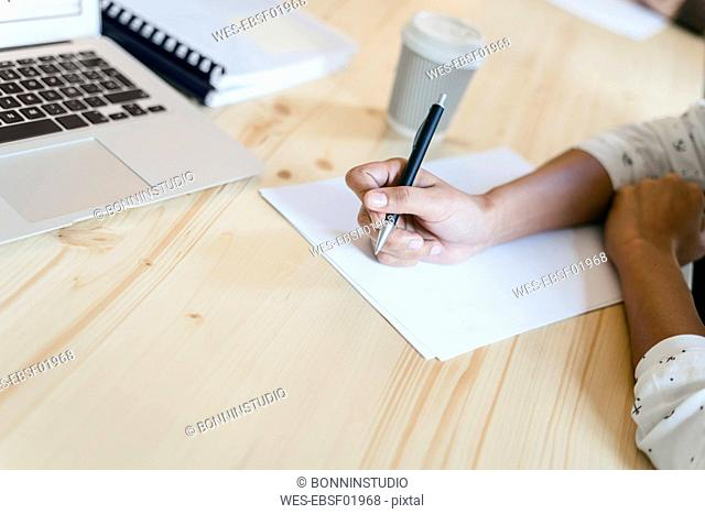 Businesswoman sitting in meeting, taking notes with a ballpen