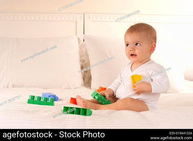 Baby playing with toy bricks on a bed