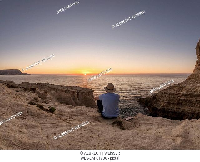 Spain, Andalusia, Cabo de Gata, back view of man looking at the sea at sunrise