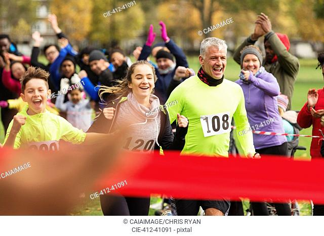 Enthusiastic family running, nearing finish line at charity run in park