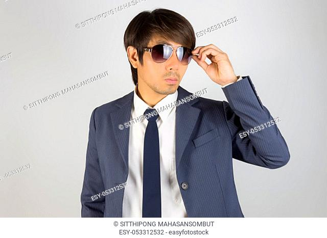 Young Asian Portrait Businessman in Navy Blue Suit Touch Sunglasses and Look Above on Grey Background
