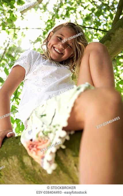 Portrait Of Young Girl Climbing Tree