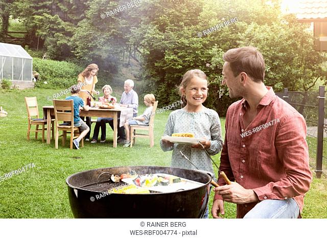 Smiling father and daughter on a family barbecue