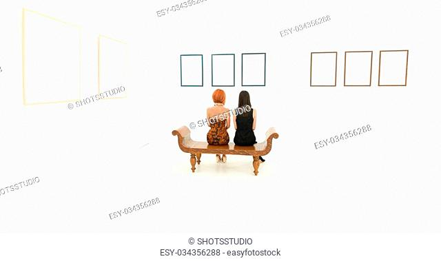 rear view of two women sitting on a wooden bench looking at empty frames displayed on a wall in front of them
