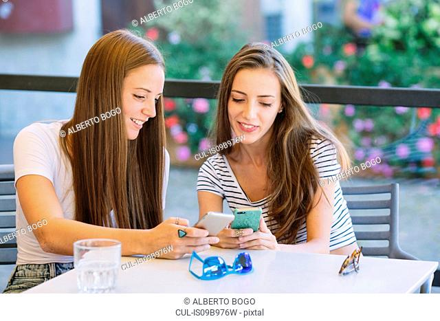 Two young female friends looking at smartphones at sidewalk cafe